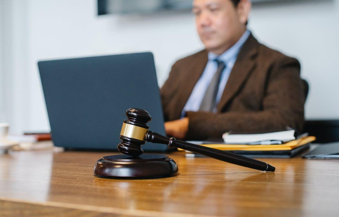 Crop concentrated Asian male judge in formal clothes sitting using modern netbook while working in law office
